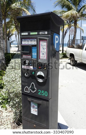 Fort Lauderdale, FL, USA - July 24, 2014: Large, electronic parking meter at Fort Lauderdale Beach Park on a sunny day with a view of the Atlantic Ocean. Digital parking meter at the beach