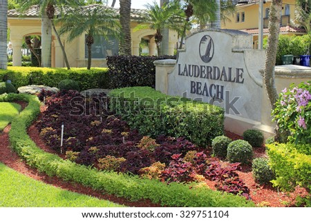 Fort Lauderdale, FL, USA - June 25, 2014: Large cement and metal Lauderdale Beach entrance sign with beautiful plants, trees, lawn and flowers around the sign. Lauderdale Beach entry sign - stock photo