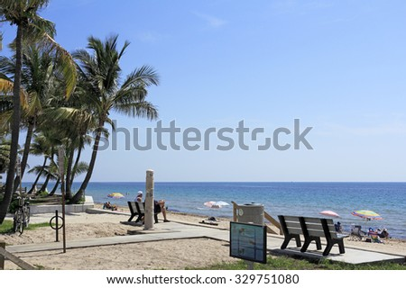 Fort Lauderdale, FL, USA - June 25, 2014: Lauderdale Beach Park Atlantic coast view being enjoyed by many people on a sunny day.  This ocean view park at the east end of 25th Street has palm trees - stock photo