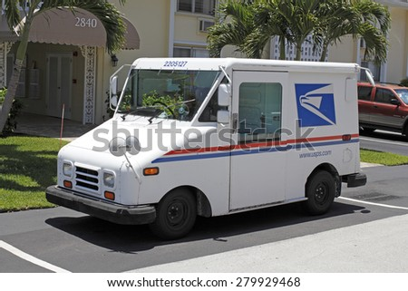 FORT-LAUDERDALE, FL, USA - JUNE 5, 2014: One deliver mail parked in front of a residential condominium on a sunny day. USPS Mail delivery truck parked on a neighborhood street.  - stock photo