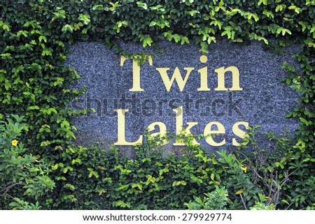 FORT-LAUDERDALE, FL, USA - JUNE 19, 2014: Twin Lakes south neighborhood entry sign in big yellow letters on a stone wall surrounded by green climbing vine foliage with some small yellow flowers.   - stock photo