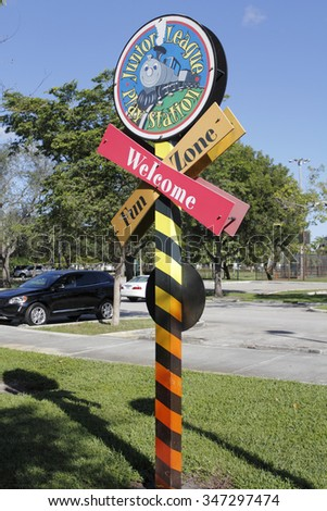 Fort Lauderdale, FL, USA - November 30, 2014: Railroad crossing shape sign welcoming people to the Junior League Play Station Fun Zone. Junior League Play Station Fun Zone entrance sign.