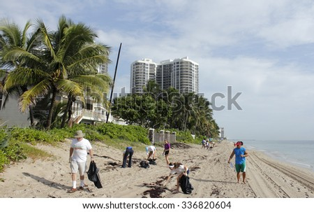 Fort Lauderdale, FL, USA - September 20, 2014: People picking up beach trash north of Oakland Park Boulevard in the yearly Ocean Conservancy International Coastal Cleanup.  - stock photo