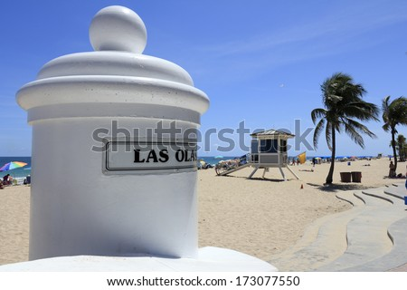 FORT LAUDERDALE, FLORIDA - APRIL 8, 2013: Entrance sign to Las Olas beach looking south along the Atlantic ocean coast with lifeguard tower 6 and many people relaxing along its sunny tropical shore.  - stock photo