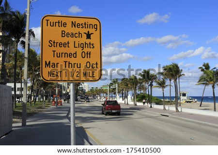 FORT LAUDERDALE, FLORIDA - JANUARY 23, 2014: A large yellow and black sign along A1A warning people visiting the beach that street lights are off at night March through October.  - stock photo