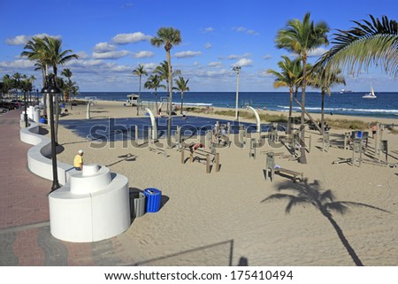 FORT LAUDERDALE, FLORIDA - JANUARY 23, 2014: Variety of people, mostly men, exercising in the public exercise equipment area and basketball courts of Fort lauderdale Beach Park on a mostly sunny day. - stock photo
