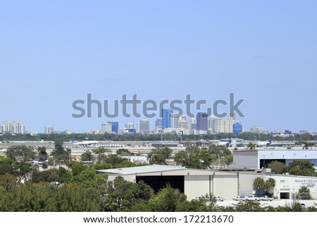 FORT LAUDERDALE, FLORIDA - MARCH 30, 2013: A commercial plane landing at Fort Lauderdale-Hollywoood International airport in front of a background of downtown Fort Lauderdale on a sunny winter day.