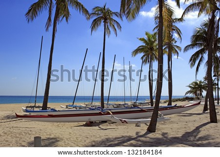 FORT LAUDERDALE, FLORIDA - NOVEMBER 1: About a dozen outrigger canoe boats available for renting to sail on the ocean north of South Beach Park on November 1, 2012 in Fort Lauderdale, Florida. - stock photo
