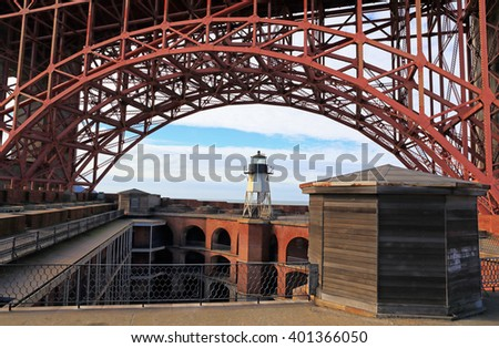 Fort Point and its lighthouse sit beneath the southern section of the famous Golden Gate Bridge. - stock photo