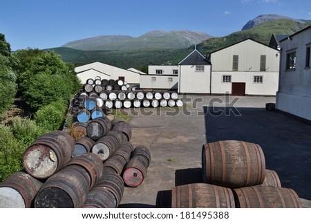 FORT WILLIAM, SCOTLAND - JULY 20: Barrels at the Ben Nevis distillery with Ben Nevis Mountain in background on 20 July 2013 in Fort William, Scotland, UK. - stock photo