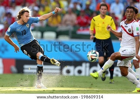 FORTALEZA, BRAZIL - June 14, 2014: Diego Forlan of Uruguay and Bolanos of Costa Rica compete for the ball during the World Cup game between Uruguay and Costa Rica at Castelao Stadium. No Use in Brazil