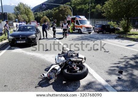 FORTEZZA, ITALY - SEPTEMBER 26, 2015: Firefighters and paramedics with ambulance cars at work after collision between car and motorbike. Accident due to high speed in city centre on September 26, 2015 - stock photo