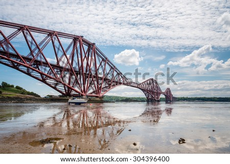 Forth Cantilever Railway Bridge / The famous Forth Cantilever Railway Bridge spans the Firth of Forth on a sunny day reflected in the wet sand at low tide - stock photo