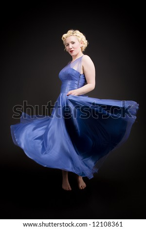 Forties hollywood a beautiful woman shows off her gown. strong eye contact. Minimal lighting and strong colour. - stock photo