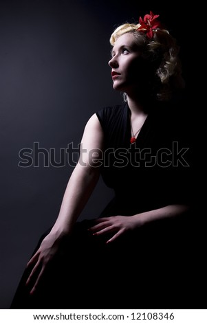 Forties hollywood a beautiful woman stares out of frame. Minimal lighting and strong contrast. - stock photo