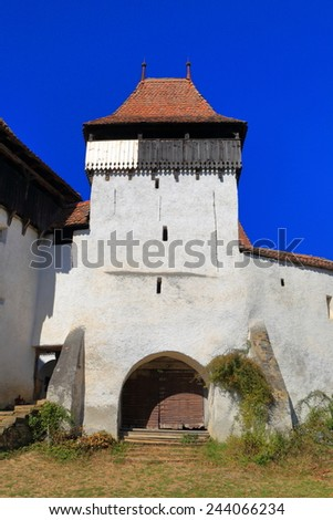 Fortified gate and tower of UNESCO world heritage church in Viscri, Transylvania, Romania - stock photo