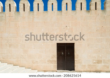 Fortified Wall around Tunsian Old Town with Entrance Door - stock photo