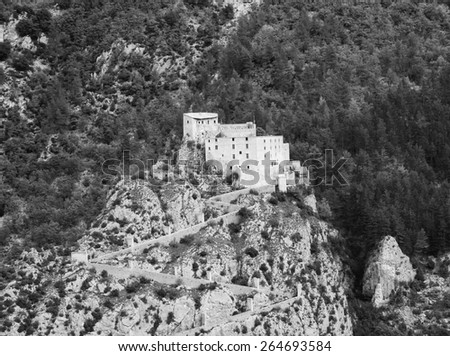 Fortress on the cliff over the medieval town of Entrevaux. (Alpes-de-Haute-Provence, France) Aged photo. Black and white. - stock photo