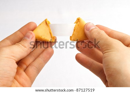 Fortune cookie being pulled apart with a blank fortune against a white background - stock photo