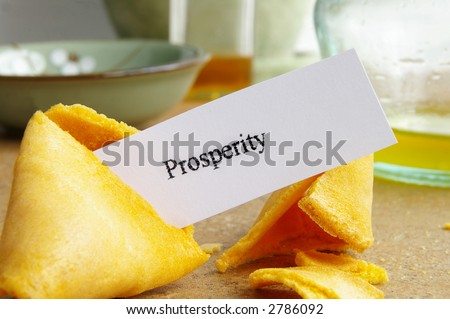 """Fortune cookie closeup with paper """"prosperity"""" message - stock photo"""