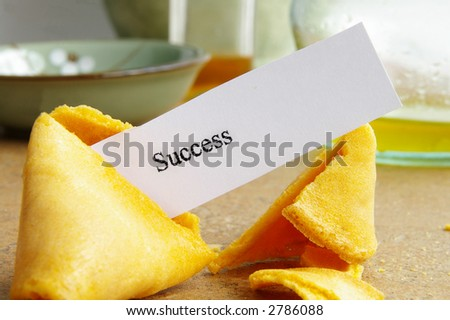"Fortune cookie closeup with paper ""success"" message"