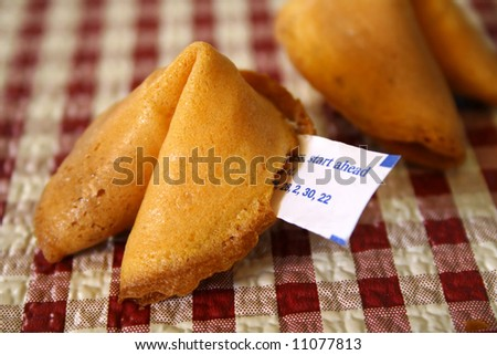 Fortune cookie on a red and white checkered background. - stock photo