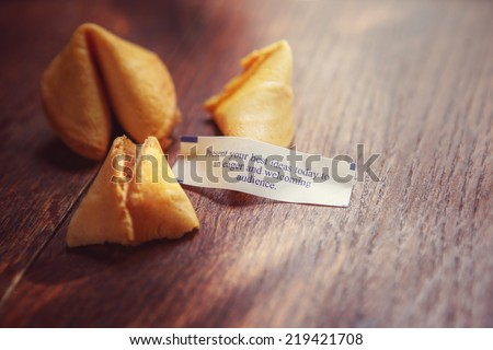 "Fortune cookie with fortune ""Present your best ideas today to an eager and welcoming audience"".  Shallow focus. - stock photo"