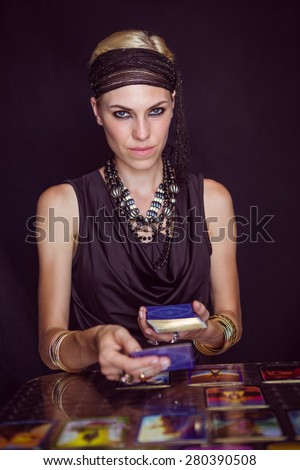 Fortune teller forecasting the future with tarot cards on black background - stock photo
