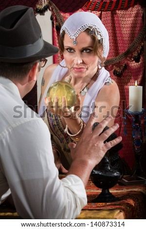 Fortune teller holding crystal ball in front of scared man