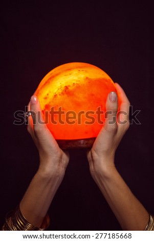 Fortune teller holding crystal ball on black background - stock photo