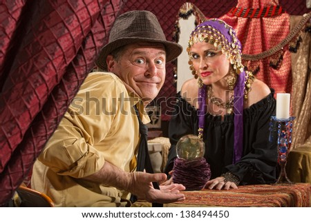 Fortune teller in head scarf with skeptical customer and crystal ball - stock photo
