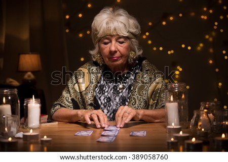 Fortune teller reading tarot cards to predict fate - stock photo