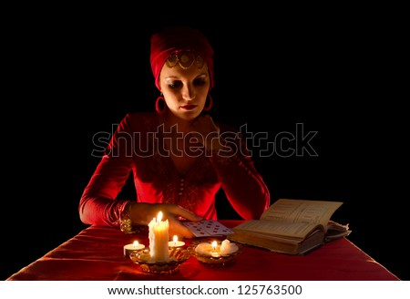 Fortune-teller sitting at the table with candles and magic book - stock photo
