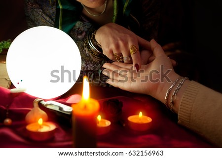 Fortune teller woman point her finger to another woman palm, palm reading