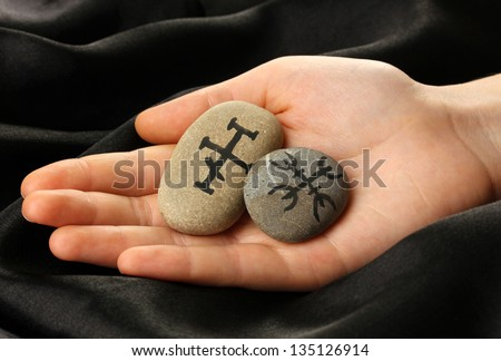 Fortune telling  with symbols on stone in hand on black fabric background