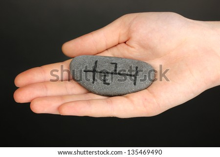 Fortune telling  with symbols on stone in hand on grey background