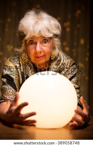 Fortuneteller looking into magic crystal ball to see the future - stock photo