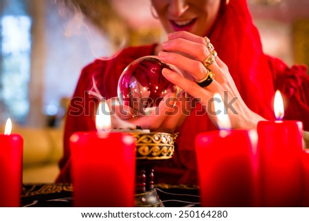 Fortuneteller or esoteric Oracle, sees in the future by looking into their crystal ball, incense burning and candles giving light - stock photo