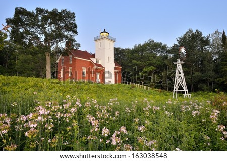 Forty Mile Point Lighthouse wild roses in bloom, Rogers City Michigan - stock photo