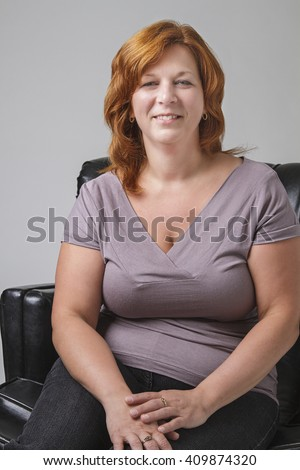 forty something woman with red hair sitting on a black leather love seat - stock photo