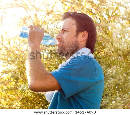 Forty years old caucasian active man drinking water and having a rest after workout during sunny summer day - stock photo