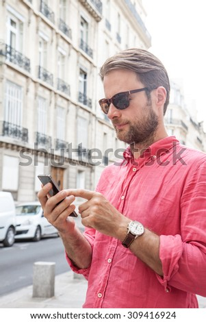 Forty years old caucasian man in sunglasses looking at mobile phone (smartphone) in Paris. Street and old city buildings as background. - stock photo