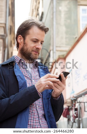 Forty years old caucasian man looking at a mobile phone. Old city buildings as background. - stock photo