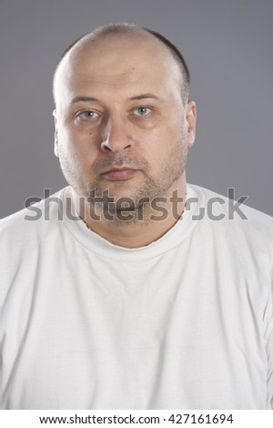 Forty years old man wearing white t-shirt  bald head looking depressed and for someone else help