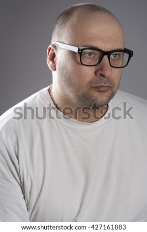 Forty years old man wearing white t-shirt black frame glasses bald head looking depressed and for someone else help
