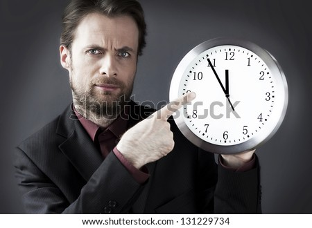Forty years old strict demanding boss with a pointing finger on a clock - indicates a deadline hour - stock photo