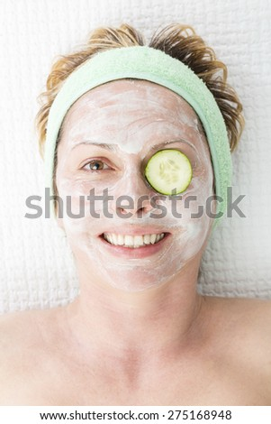 Forty years woman with face mask and cucumber - stock photo