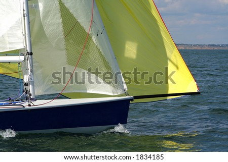 Forward to a victory under sails! The modern sports yacht rushes on the large speed. Yellow and white sails. - stock photo