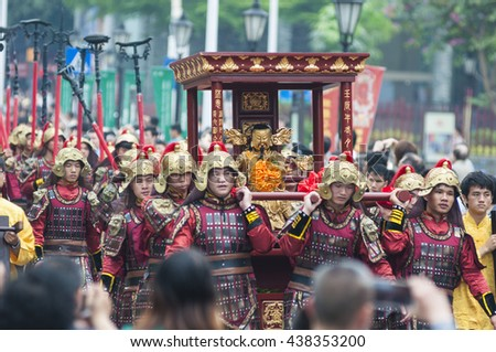 FOSHAN, CHINA - April 9, 2016: Taoist god's birthday, and dozens of wearing traditional dress man carried the god cruise, honor guard, dancing, lion and other art team took part in the parade. - stock photo