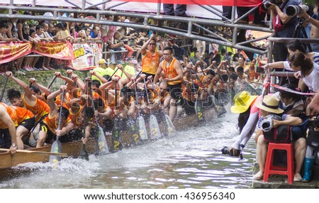 FOSHAN, CHINA - June 12, 2016: the Dragon Boat Festival dragon boat race held in the pile of beijiao river, there were 18 teams, cloud team won the championship, attracted thousands of people watched. - stock photo